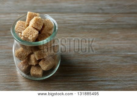 Glass jar with brown lump sugar on wooden table