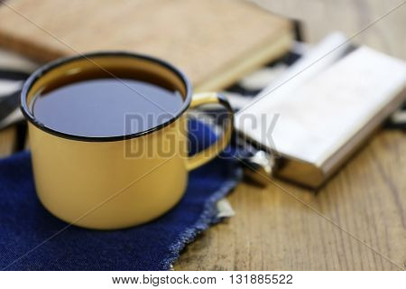 Cup of strong coffee with a flask on a wooden table, close up