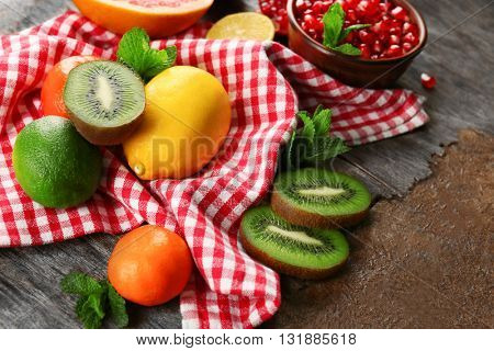 Juicy composition of tropical fruits on wooden background