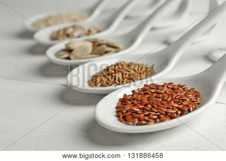 Different kinds of seeds in spoons on wooden table