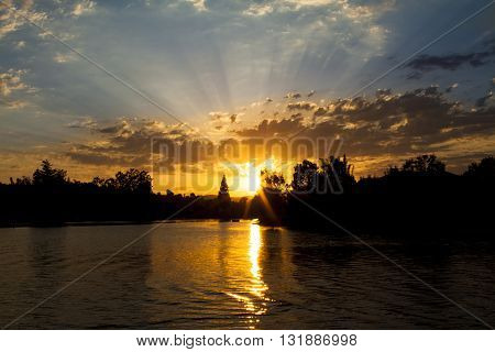 A lake lined with trees at sunset with cloudy sky and God's rays.
