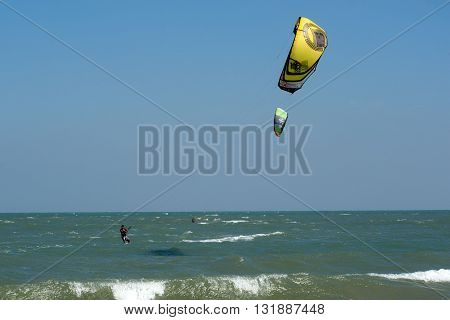 PHRACHUAP KHIRI KHUN,THAILAND-DECEMBER 20,2013 : Kite surfers in  the sky of Phranburi sea near Phranburi District. Kite surfing is a popular water sport in Phrachuap Khiri Khun Province,Thailand.