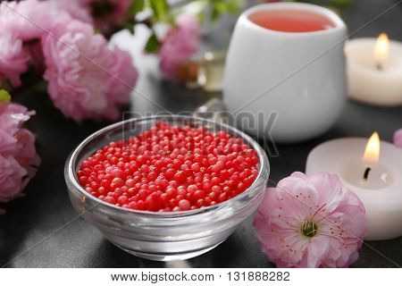 Spa composition with beautiful flowers and bath pearls on the table, close up