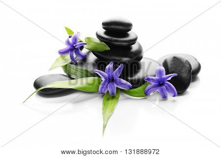 Stack of spa hot stones and flowers isolated on white