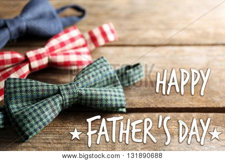 Happy Father's Day. Male bow ties on wooden background