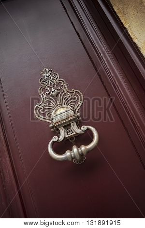 Detail of an old bronze knocker on the door of a French mansion