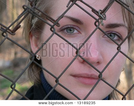 Girl is crying behind a metal fence