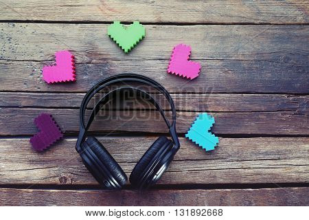 Black headphones with hearts on wooden background