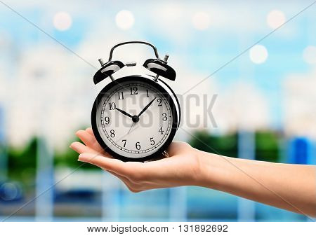 Female hand holding old clock in hand on blurred background