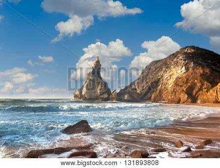 Summer ocean shore, fantastic rock, stones and water waves on the beach, blue sky. Portugal, Europe