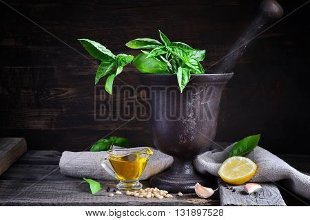 italian recipe ingredients for basil pesto on a dark background style rustic