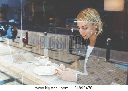 Woman is chatting via mobile phone in social networkwhile is resting after on-line learning via laptop computer during her recreation time in coffee shop.Hipster girl is reading message on cell phone