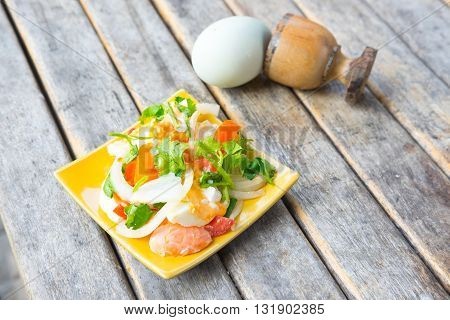 Spicy salad with salted eggs on yellow dish