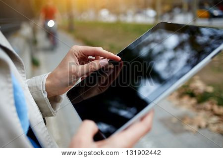 Closely image of hipster girl is working on portable computer with empty copy space screen. Close up of woman is navigating way in internet via digital tablet during walking in an unfamiliar city