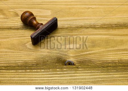 Wooden stamp on a brown wooden background texture