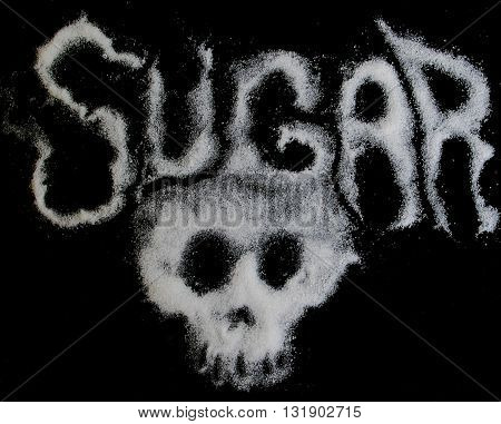 Negative sugar health concept with sugar shaped into ghostly letters and skull on black background.