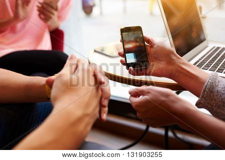 Closeup image of two person are watching video in internet via cellphone while they are sitting in hipster coffee shop interior. Closely of woman`s hand is holding mobile phone with copy space screen