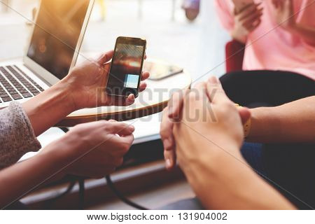 Closely of hand is holding cell phone with copy space screen for your advertising content. Two person are watching video in internet via mobile phone while are sitting near open net-book on the table