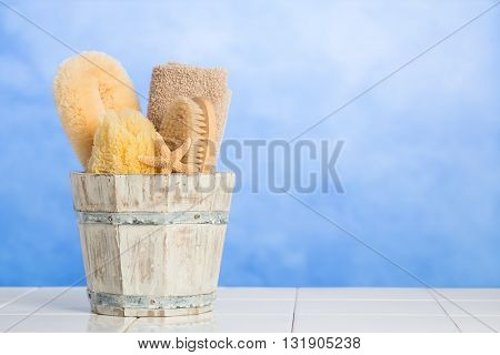 Spa items in wooden bucket with fresh blue background - plenty of copy space for advertising