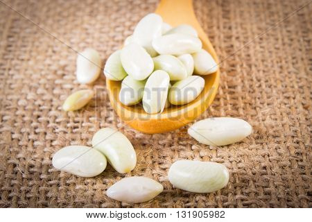 Seeds of beans on wooden spoon lying on jute canvas healthy food and nutrition