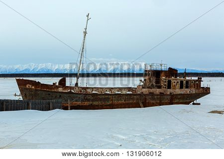 Old rusty ship on the winter shore of Lake Baikal.