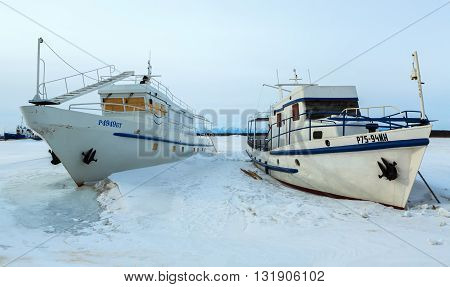 Ust-Barguzin, Russia - March 04, 2016: Ship in frozen lake covered with snow in winter evening