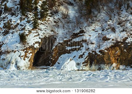 Cave in the rock with icicles. Beautiful winter landscape in the Lake Baikal.