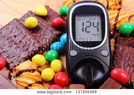 Glucose meter with heap of candies and cookies on wooden table too many sweets concept of diabetes and reduction of eating sweets