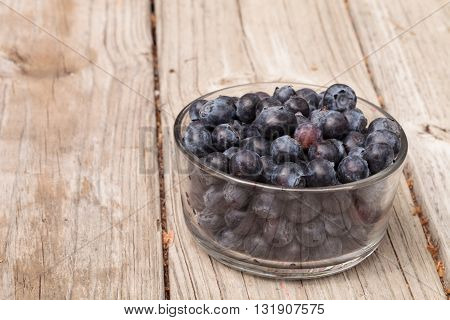 Clear glass bowl of ripe blueberries on a rustic farm picnic table in summer.