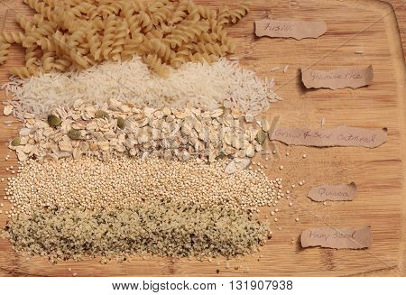 Multiple organic grains, including fusilli, jasmine rice, quinoa, hemp seed, and a mix of grains and seeds oatmeal, on a cutting board on a rustic farm picnic table in summer.