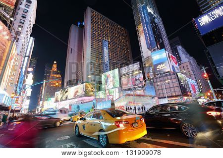 NEW YORK USA - APRIL 12: The architecture of the famous Times Square in New York city USA with its neon lights and panels at night and a lot of tourists passing by on April 12 2016.