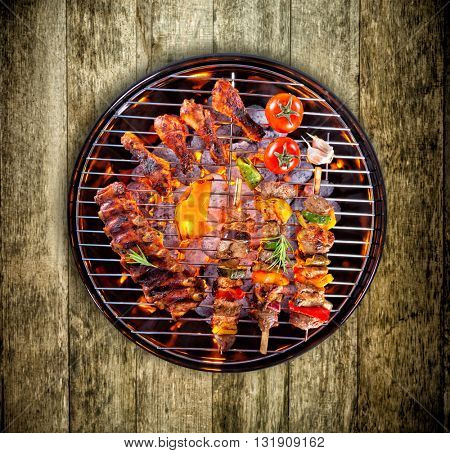 Pork ribs, chicken legs, skewers and vegetable served on grill, wooden planks as background