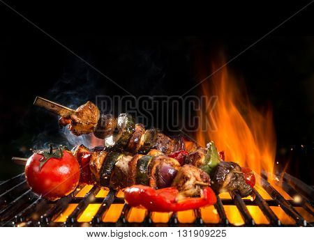 Meal skewer on grill with fire, isolated on black background