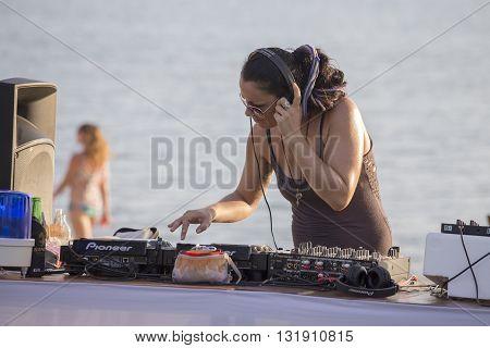 KOH PHANGAN THAILAND - DECEMBER 12 2015 : Girl DJ at beach club playing mixing music on vinyl turntable before Full Moon party on island Koh Phangan.