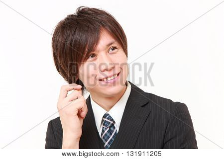 portrait of young Japanese businessman thinks about something on white background