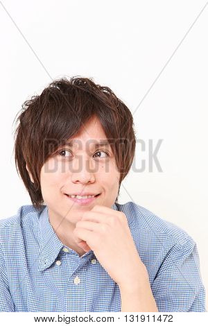 portrait of young Japanese man thinks about something on white background