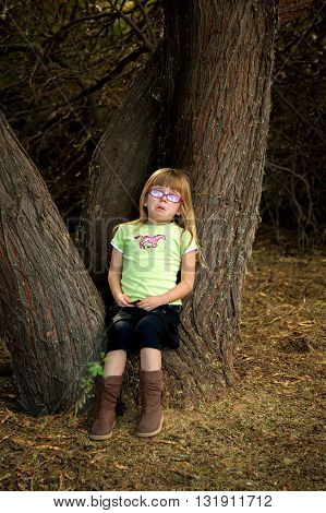 A little girl sits in the crook of a tree base crying. She was on a hike and did not want to walk any further. She is wearing glasses and has a tear on her cheek.