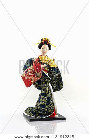 Japanese geisha dolls with folding fan on white background.