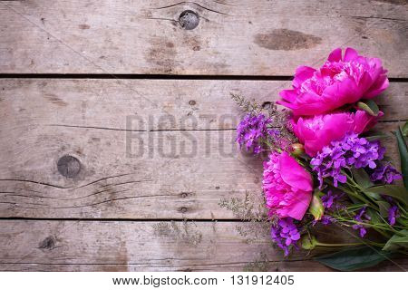 Pink peonies flowers on aged wooden background. Flat lay. Top view with copy space. Selective focus.