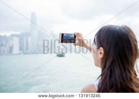 Woman using mobile phone for taking photo