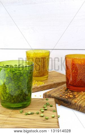 Multicolored clear glasses with various legumes ( green peas red lentils yellow indian lentils) on olive wood background