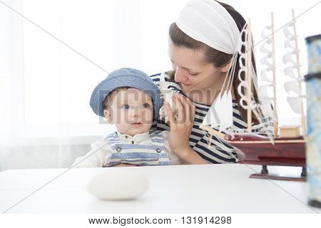 Mother And Her Baby Boy With Seashell.