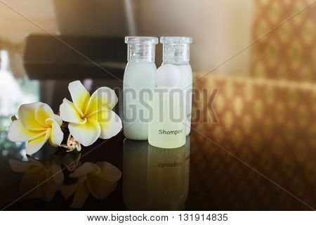 Mini set shampoo and bath soap liquid amd conditioner gel with flowers plumeria or frangipani on black counter in vintage relaxing and spa mood classic and soft colour shower bath set with copy space