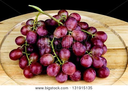 Bunch of grapes on a wooden tray on black background
