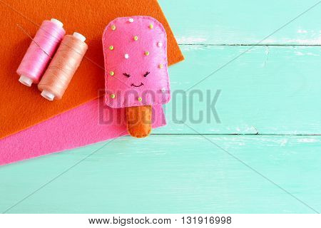 Adorable felt ice cream toy. Felt play food pattern. DIY felt food. Easy fabric crafts for kids. Thread, brown and pink wool sheets. Summer fun background.