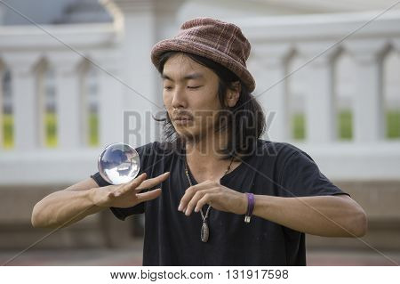 BANGKOK THAILAND - JANUARY 22 2015: Unknown street performer juggling glass bowl in front of passers-by on the street Khao San Road in Bangkok