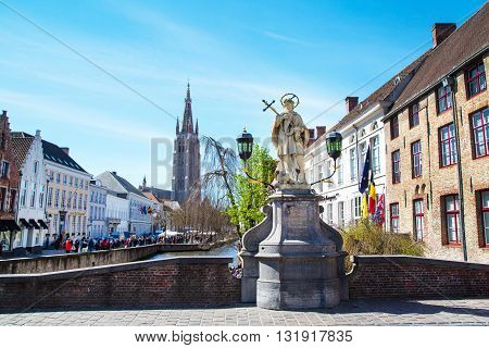Bruges, Belgium - April 10, 2016: Scenic cityscape with houses, statue of Johannes Nepomucenus, church tower Bruges, Belgium