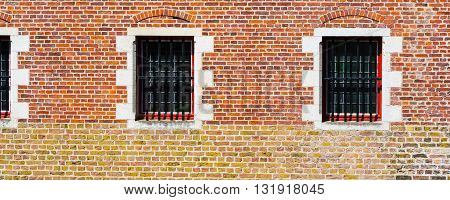 Windows of traditional medieval house exterior on red brick wall in Brugge, Belguim, panoramic background