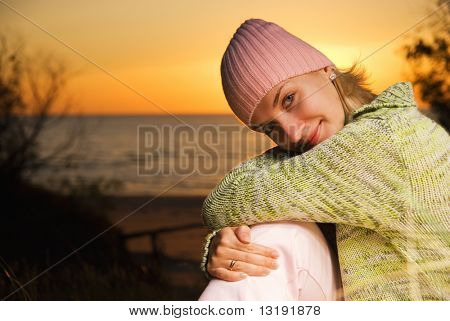 Young girl sitting on the beach at sunset time