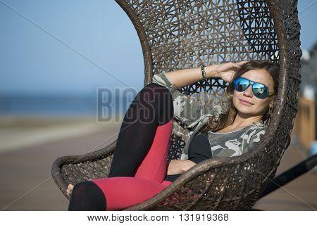 Woman Sitting On A Wicker Swing Outdoor